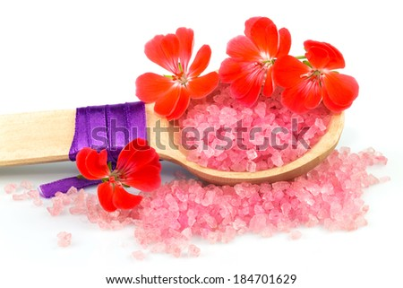 Macro view of wooden spoon with pink bath salt and red flowers isolated on white background - stock photo