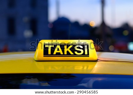 Macro view of yellow turkish taxi sign on car at night with a colourful bokeh of urban lights. - stock photo