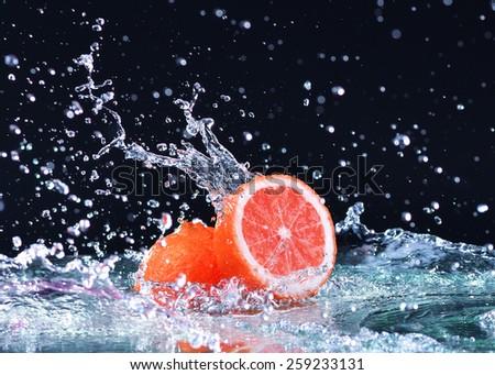 Macro water splash on grapefruit. Water drops with juicy grapefruit - stock photo