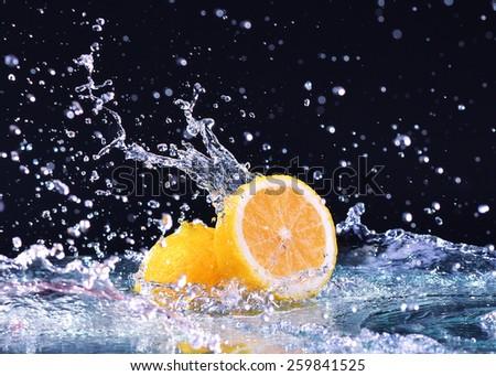 Macro water splash on lemon. Water drops with juicy lemon - stock photo