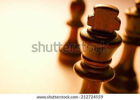 Macro Wooden King Chess Piece on White Background. King Piece is the Highest Royalty in Chess Board Game. - stock photo