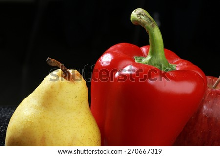 macro yellow pear, red apple and red bell peppers on black background studio - stock photo