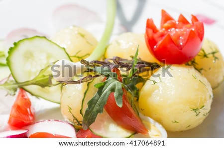 Macro young potatoes with dill and cherry tomato