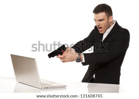 mad and angry young businessman destroying his laptop using guns - stock photo