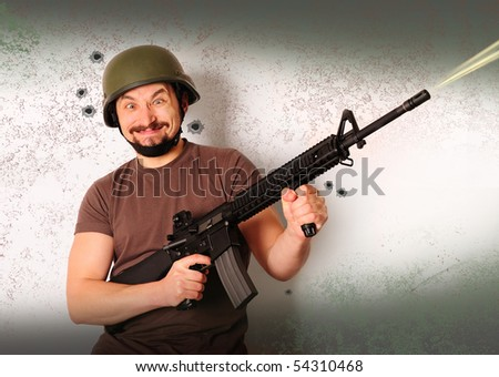 Mad armed man in protective helmet shooting on a grunge background