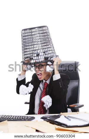 Mad Asian businessman with trash bin on his head isolated on white - stock photo