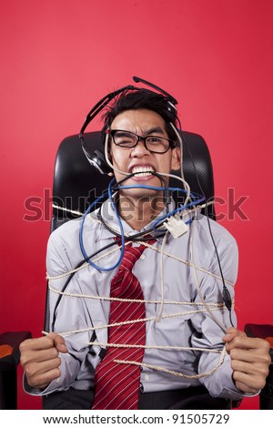 Mad customer service staff tied up on chair - stock photo