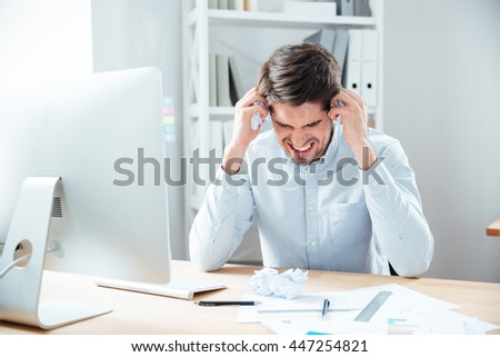 Mad desperated young businessman sitting in office - stock photo