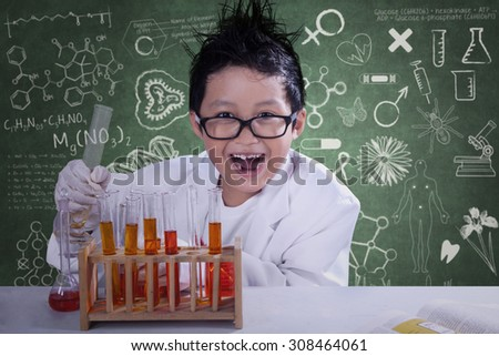 Mad little scientist doing experiment with chemical fluid and looking at camera - stock photo