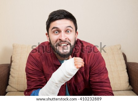 Mad man in red shirt sitting on couch and holding his broken hand