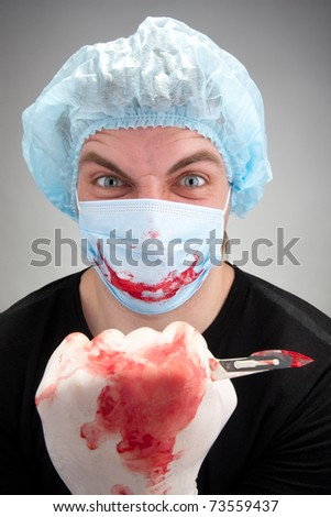 Mad mental sick blood soiled surgeon with knife - stock photo