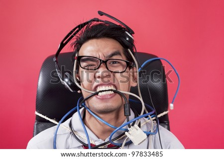 Mad operator with cables and rope, shot in studio on red background - stock photo