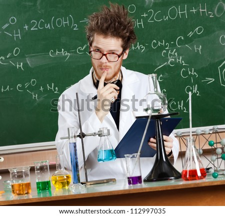 Mad professor considers the results of tests in his laboratory - stock photo