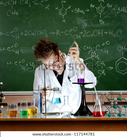 Mad professor holds an experiment in his laboratory - stock photo