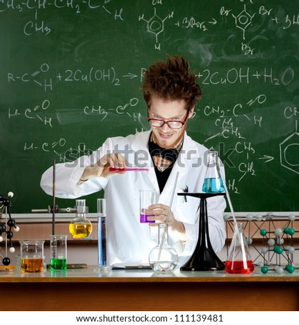 Mad professor pours some red liquid in beaker while making an experiment in his laboratory - stock photo