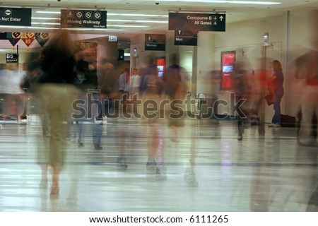 mad rush of passengers at the airport going down the concourse toward the planes. - stock photo