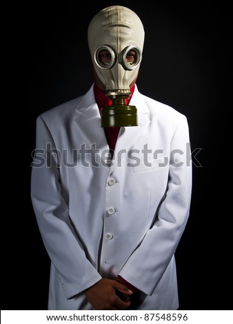 mad scientist wearing a gas mask and a lab coat - stock photo