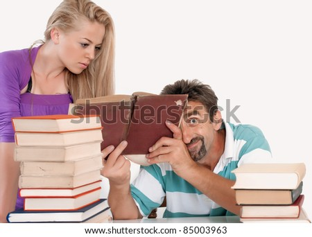 Mad teacher holding book and making faces - stock photo