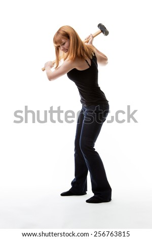 mad woman swing a sledge hammer over her head at the ground - stock photo