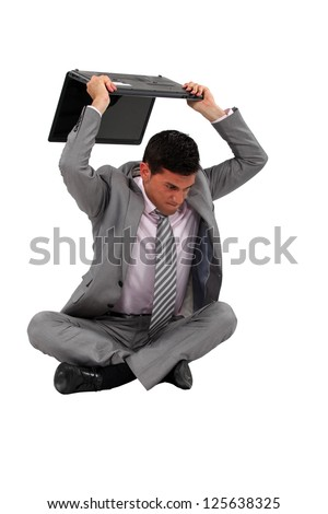 Mad worker destroying computer - stock photo