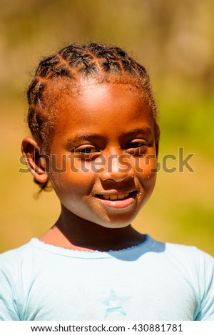 MADAGASCAR - JUNE 27, 2011: Unidentified Madagascarian girl smiles for the camera in Madagascar, June 27, 2011. Children of Madagascar suffer of poverty due to the unstable situation.