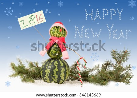 made from watermelon Snowman  in red hat and scarf with candy cane on blue background and falling snowflakes. Holiday concept for New Years with  inscription 2016 - stock photo