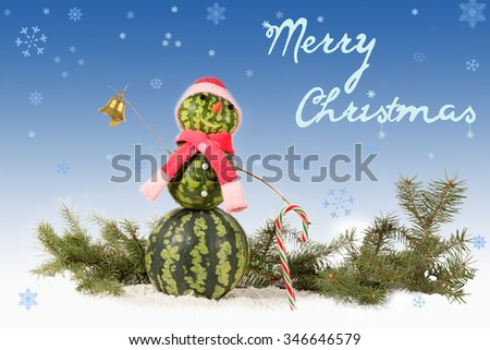 made from watermelon Snowman  in red hat and scarf with candy cane on blue background and falling snowflakes. Holiday concept for Merry Christmas with  inscription - stock photo