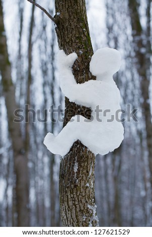 Made of snow man crawling on a tree - stock photo