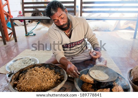 MADHYA PRADESH, INDIA - DEC 28: Adult man makes fire to cook the traditional indian village bread in the metal pot on December 28, 2012 in Chitracoot. Population of Chitrakoot is 22,294 people - stock photo