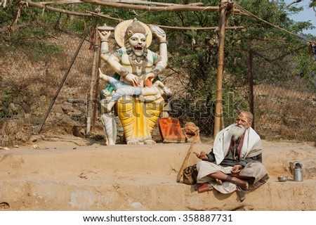 MADHYA PRADESH, INDIA - DEC 30: Poor man in clothes of Indian pilgrim resting by the sculpture of the hindu god Narasimha on December 30, 2012 in Chitrakoot city. Population of Chitrakoot is 22,294