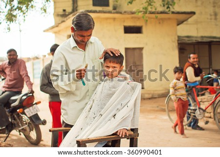 MADHYA PRADESH, INDIA - DEC 29: Unidentified preschool child with unhappy face doing new hairstyle by village barber on December 29, 2012 in Chitrakoot. Populatation of Chitrakoot is 22,294 - stock photo