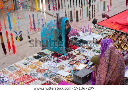 MADHYA PRADESH, INDIA - DEC 22: Women traded over a tray with cheap jewelry and colorful beads on December 22, 2012 in Orchha. Madhya Pradesh is the second largest indian state by area - stock photo