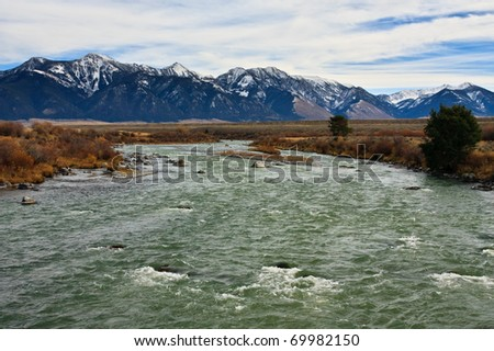Madison River flowing in front of the steep Bridger Mountain Range, Montana. - stock photo