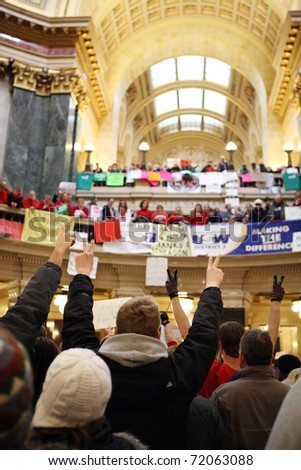 MADISON, WI - FEB 21: Protesters against budget cuts for public workers hold up peace signs inside the state capitol on Feb 21, 2011 in Madison Wisconsin. - stock photo