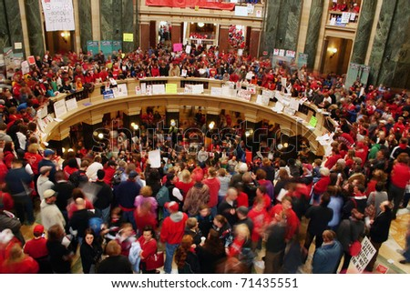 MADISON, WI - FEB 17: Thousands fill the capitol protesting Wisconsin Gov Scott Walker's proposal to eliminate collective bargaining rights for public workers on Feb 17, 2011 in Madison Wisconsin. - stock photo