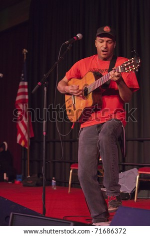 MADISON, WI - FEB. 21: Tom Morello, The Nightwatchman, performs at the Monona Terrace in Madison, WI on February 21, 2011 to rally for worker's rights in an anti-Walker protest. - stock photo