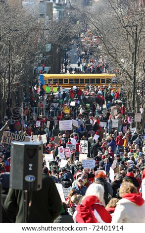 MADISON, WI - FEB 19: Unidentified people protest WI Budget Repair Bill on February 19, 2011 looking down State Street in Madison, WI.  Thousands of people gather to march and protest the bill. - stock photo