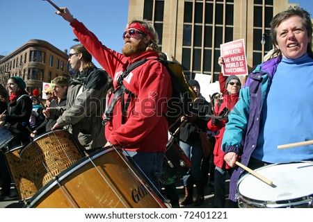 MADISON, WI - FEB 19: Unidentified people protest WI Budget Repair Bill on February 19, 2011 on the capitol square in Madison, WI.  The drummers lead many people marching in protest of the bill. - stock photo