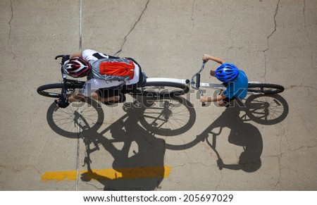 MADISON, WI-JULY 13: A man rides a bike with his son along the bike path in front of the Monona Terrance on a sunny Sunday afternoon. - stock photo