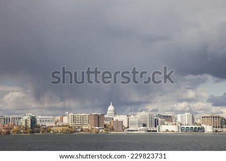 Madison, Wisconsin, USA - October 27, 2011: Madison, WI cityscape, storm clouds and Lake Monona in foreground.   - stock photo