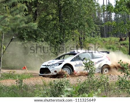 MADONA, LATVIA-JUNE 9: Vasily Gryazin and Dmitry Chumak drives Ford Fiesta S2000 during a motoring event Rally Madona 2012 in Madona, Latvia on June 09, 2012. - stock photo