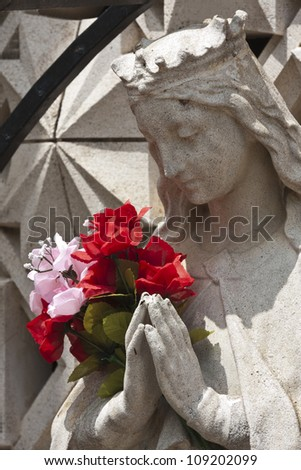 Madonna statue praying with bouquet placed on hands - stock photo