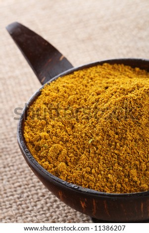 Madras Curry Powder in coconut bowl, on brown hessian background, shallow DOF