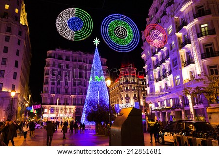 MADRID - DECEMBER 31, 2014: Calle de la Montera crowded with tourists on December 31 in Madrid. An illuminated Christmas tree and festive decorations light up the street each year for the holidays. - stock photo