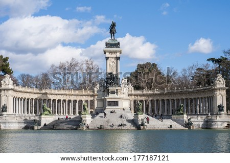 MADRID, ES - JANUARY 21, 2013: People walking near Monument to King Alfonso XII (Monumento a Alfonso XII), situated on the east edge of the artificial lake near the center of the Buen Retiro Park.