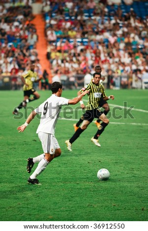 MADRID - JULY 26 : Cristiano Ronaldo (L) of Real Madrid prepares a cross in his first match during Peace Cup competition at Santiago Bernabeu stadium July 26, 2009 in Madrid. Real Madrid 1-1 draw with Al Ittihad. - stock photo