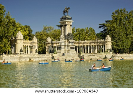 MADRID - JULY 29: The Monument to Alfonso XII, tourists boating in a lake people enjoy summer evening in Buen Retiro Park, is the large and popular 1.4 km2 park, on July 29, 2012 in Madrid, Spain