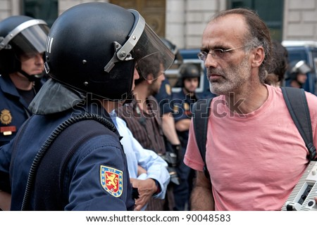 MADRID - MAY 26: Spanish Protester walking to the congress building against the spanish economic crisis and pensions for the politicians and stopped by the police on May 26, 2011. - stock photo
