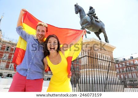 Madrid people showing Spain flag on Plaza Mayor cheerful and happy in Spain. Cheering celebrating young woman and man holding and showing flags to camera on the famous square in front of statue. - stock photo