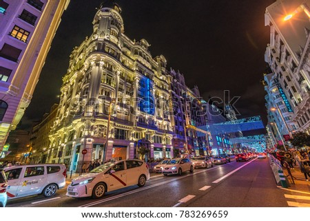 Madrid, Spain - December 26, 2017 : People, crossing Gran Via street, enjoing Christmas lights decoration and shopping during Christmas season. Madrid is the capital and the largest city of Spain